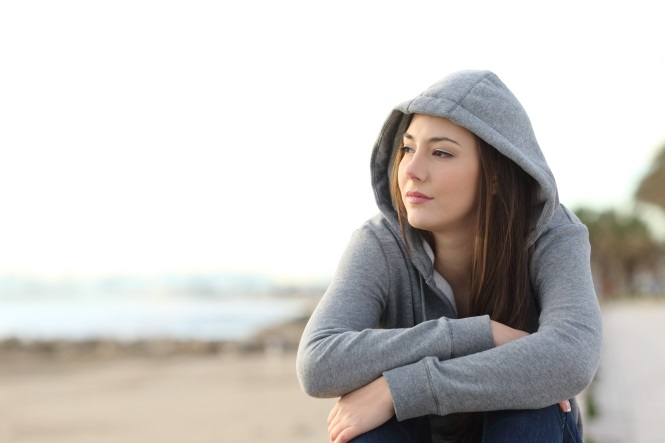 woman in a hoodie sitting on a beach